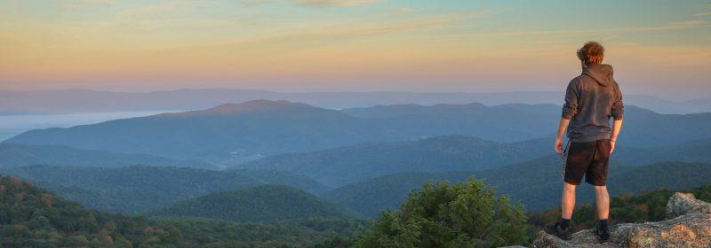 man overlooking mountainside
