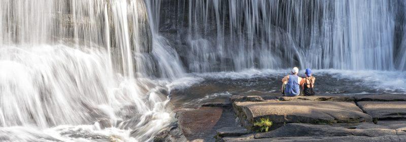 couple sitting near waterfall